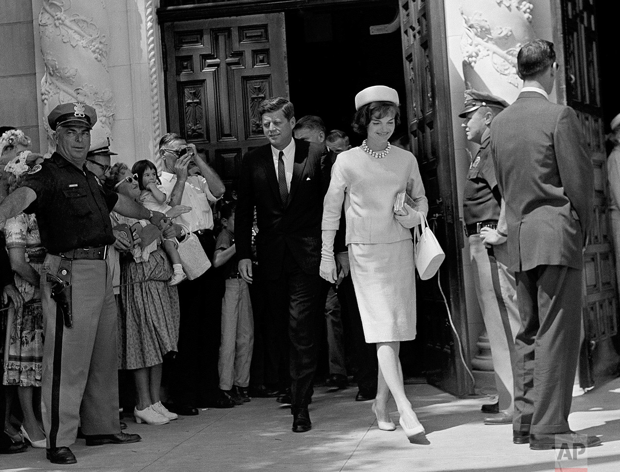 President John F. Kennedy and first lady Jacqueline Kennedy leave St. Edward's Catholic Church in Palm Beach, Fla., after attending Easter Sunday services, April 2, 1961. At left, a policeman stands in front of part of crowd that gathered to see the president and first lady who, with a reported plot threatening them and their family, were guarded by extra secret service detail. Mrs. Kennedy is wearing a pale blue two-piece shantung silk dress and matching pillbox hat. Shoes, handbag and gloves are beige. Kennedy is wearing a navy pin-striped suit. (AP Photo)