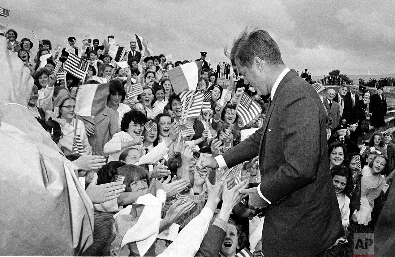 U.S. President John F. Kennedy arrives at Sean O'Kennedy soccer field and is greeted by school children waving Irish and American flags, during his visit to New Ross, Ireland, June 27, 1963. (AP Photo)