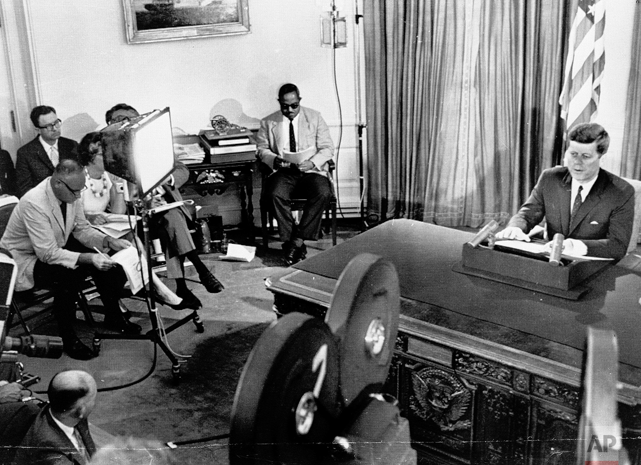 President John F. Kennedy, speaking on national TV and radio hookup from the White House in Washington, D.C., states the nation's firm position on the Berlin situation, July 25, 1961. Hand-picked newsmen representing American and foreign interests, listen off camera at left. Front row from left to right are:  Jack Sutherland, U.S. News and World Report; Mary McGrary, Washington Star; Ed Morgan, ABC. Rear from left to right are: Tom Wicker, New York Times; Anthony Goodman, Reuters; Vladimir Vashedchenko, Tass, the official Russian news agency. Far right, seated is Andrew Hatcher, White House Assistant Press Secretary. (AP Photo/Byron Rollins)