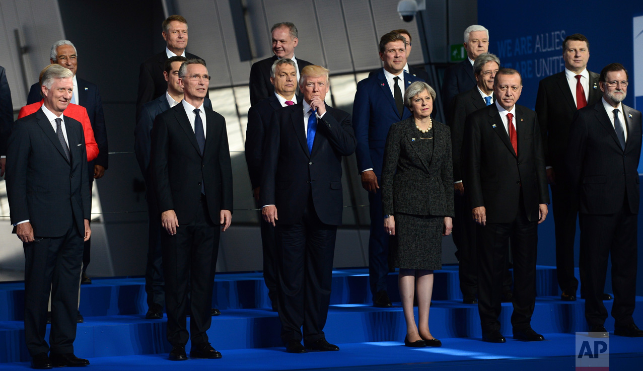 U.S. President Donald Trump, center, flanked by British Prime Minister Theresa May, third from right, and NATO Secretary General Jens Stoltenberg, second from left, joins fellow leaders in a group photo at NATO headquarters during the NATO Summit in Brussels, Belgium on Thursday, May 25, 2017. (Sean Kilpatrick/The Canadian Press via AP)