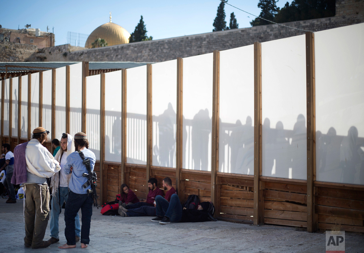 Jewish men and women gather next to the Western Wall, the holiest place where Jews can pray, in Jerusalem's Old City, during Jerusalem Day celebrations on Wednesday, May 24, 2017, commemorating the capture of the city's eastern sector in the 1967 Mideast war. (AP Photo/Ariel Schalit)