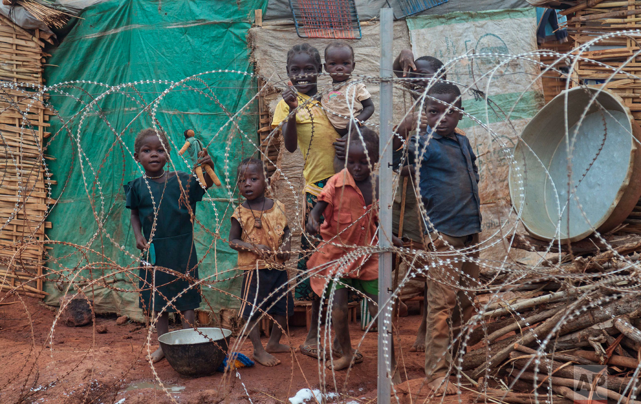 In this photo taken Sunday, May 14, 2017, a family stands behind the razor-wire that surrounds the United Nations' protected camp, to protect them in Wau, South Sudan, which since clashes in April is now the most congested internally displaced camp in the country, with almost 40,000 inhabitants.(AP Photo)
