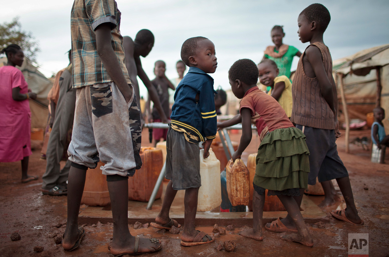 In this photo taken Sunday, May 14, 2017, children queue to carry water from a well in plastic containers at the United Nations' protected camp in Wau, South Sudan, which since clashes in April is now the most congested internally displaced camp in the country, with almost 40,000 inhabitants. (AP Photo)