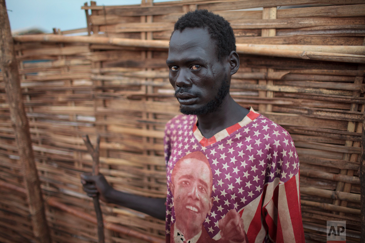In this photo taken Sunday, May 14, 2017, new arrival Madut Quat, who fled from government soldiers with his family, wears a T-shirt depicting Barack Obama as he stands in the overcrowded United Nations' protected camp in Wau, South Sudan, where his family sleep on the mud-soaked ground as they wait to be allocated shelter.(AP Photo)