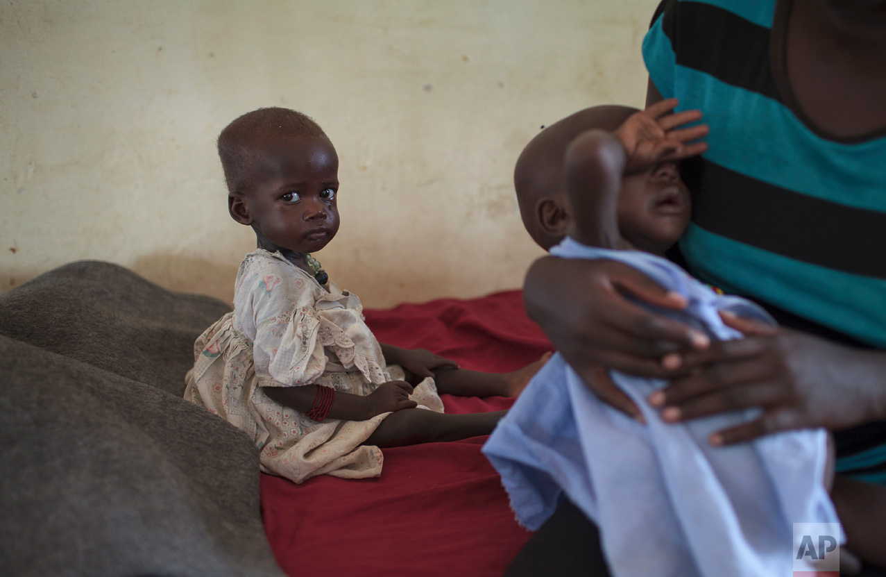 In this photo taken Wednesday, May 10, 2017, Nyataba, 1, left, sits in the State Hospital in Torit, where she is being treated for malnutrition, in southeastern South Sudan. (AP Photo)
