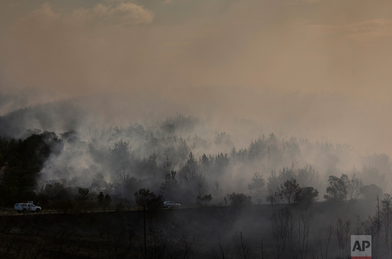 Fires smolder in Knysna, South Africa, Thursday, June 8, 2017. Fatal fires fanned by high winds spread to nearby Plettenburg Bay and Knysna in the Western Cape Province, destroying homes and forcing the evacuation of thousands. (AP Photo/Halden Krog)