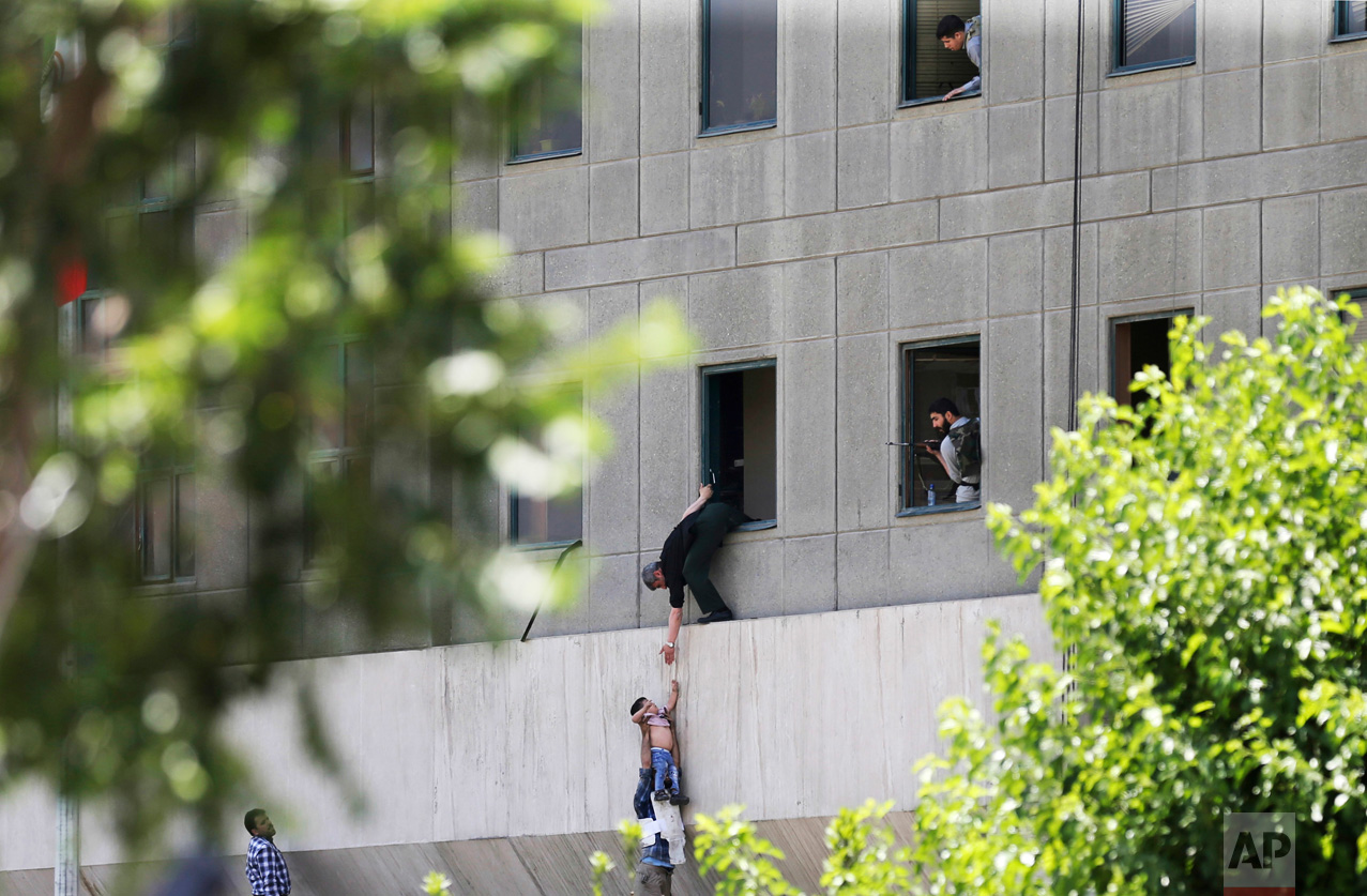 A man hands a child to a security guard after an assault on the parliament building in Tehran, Iran, on Wednesday, June 7, 2017. Suicide bombers and gunmen simultaneously targeted the legislature and a shrine of late founder of the Islamic Republic Ayatollah Ruhollah Khomeini. (Fars News Agency, Omid Vahabzadeh via AP)
