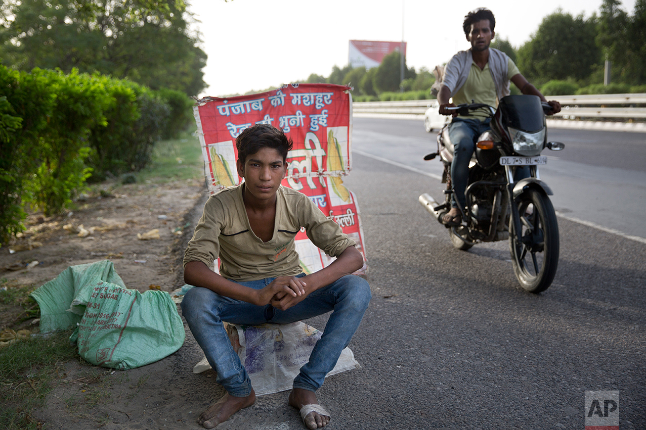 In this Tuesday, June 6, 2017 photo, an Indian boy who sells corn along a busy expressway poses for a photo next to his corn stall as a man on a motorcycle patrols to ensure business runs smoothly in Noida, India. Every 100 meters (330 feet) or so there are children selling corn along this busy expressway on the outskirts of New Delhi. According to India's 2011 census, boys like him are part of the estimated 8.3 million child laborers In India. Uttar Pradesh state, where Noida is located, alone accounts for 1.8 million of that total. (AP Photo/Tsering Topgyal)