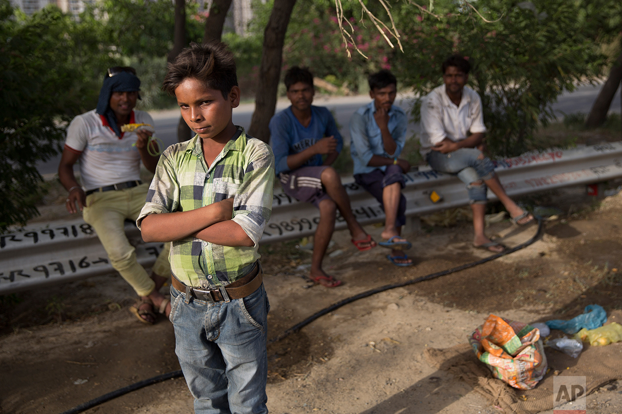 In this Tuesday, June 6, 2017 photo,  an Indian boy who sells cooked corn along a busy expressway and says he earns five thousand Rupees a month poses for a photo in Noida, India. Every 100 meters (330 feet) or so there are children selling corn along this busy expressway on the outskirts of New Delhi. According to India's 2011 census, boys like him are part of the estimated 8.3 million child laborers In India. Uttar Pradesh state, where Noida is located, alone accounts for 1.8 million of that total. (AP Photo/Tsering Topgyal)