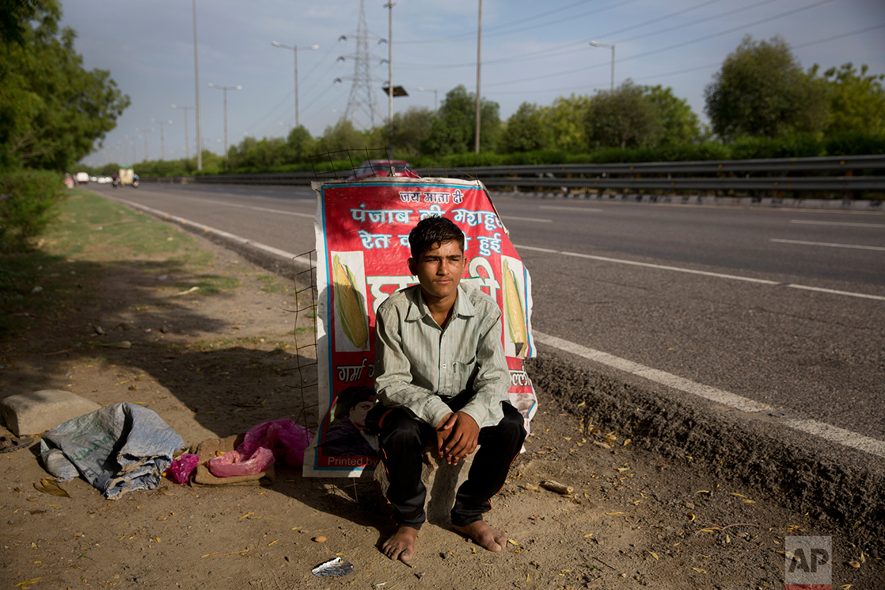 In this Thursday June 8, 2017 photo, Indian boy Bhure, poses as he sits near his make shift corn stall along a busy expressway in Noida, India. Bhure says he at times receives job offers from some of his customers promising double of what he earns. Every 100 meters (330 feet) or so there are children selling corn along this busy expressway on the outskirts of New Delhi. According to India's 2011 census, boys them him are part of the estimated 8.3 million child laborers In India. Uttar Pradesh state, where Noida is located, alone accounts for 1.8 million of that total. (AP Photo/Tsering Topgyal)
