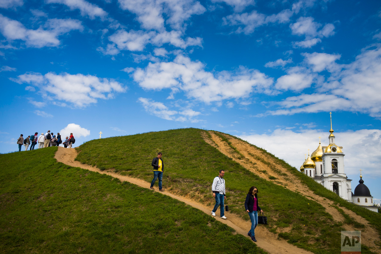 Tourists walk down from a hill near an Assumption Cathedral built in the 16th Century in the small Russian town of Dmitrov, Russia, 75 kilometers (47 miles) north from Moscow on Sunday, June 11, 2017. (AP Photo/Alexander Zemlianichenko)