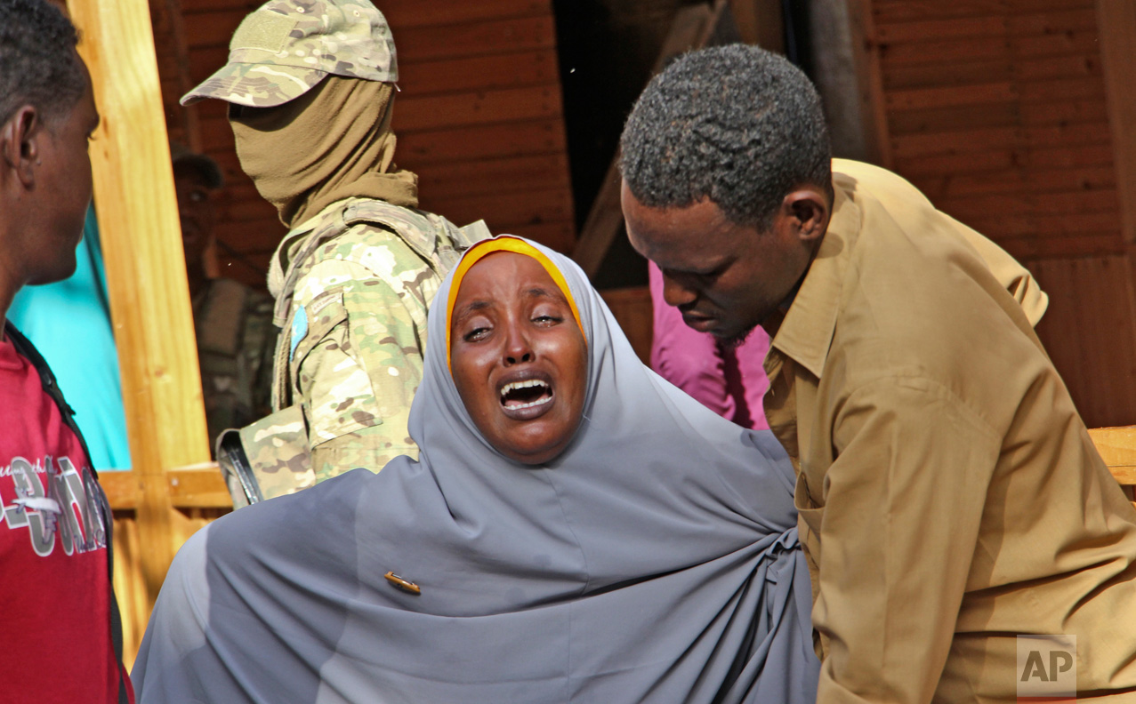 """A mother whose daughter was shot in the head by attackers during a militant attack on a restaurant, grieves in Mogadishu, Somalia, on Thursday, June 15, 2017. Somalia's security forces early Thursday morning ended a night-long siege by al-Shabab Islamic extremists at the popular """"Pizza House"""" restaurant in the capital. (AP Photo/Farah Abdi Warsameh)"""