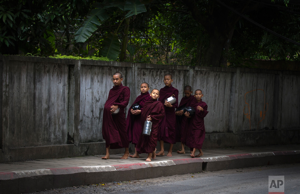 """Buddhist monks walk to collect their morning """"alms"""" (offerings) in Yangon, Myanmar, on Friday, June 16, 2017. (AP Photo/Thein Zaw)"""