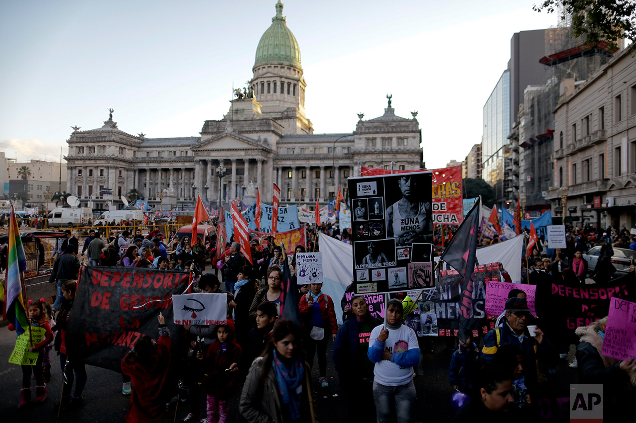 "In this June 3, 2017 photo, Maira Maidana, bottom right, holds a banner with pictures of herself during a march organized by the movement ""Ni Una Menos,"" or Not One Less,  to protest violence against women in Buenos Aires, Argentina. ""With Ni Una Menos, women are no longer hiding,"" says Maidana, 29, who is scarred in her neck and chest after her partner burned her in 2011. (AP Photo/Natacha Pisarenko)"