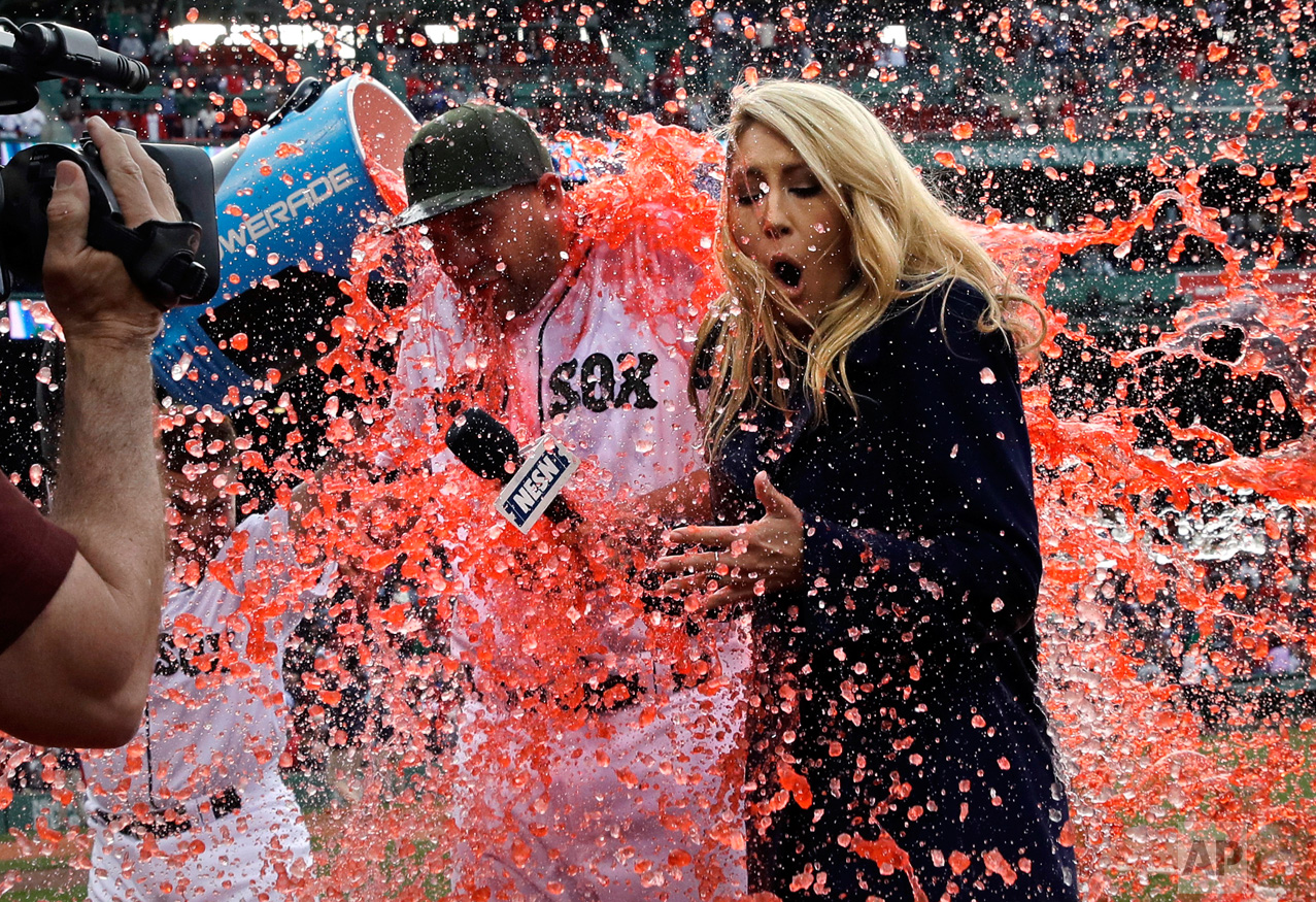 Boston Red Sox starting pitcher Brian Johnson, left, and television field reporter Guerin Austin are doused after a baseball game against the Seattle Mariners at Fenway Park in Boston, Saturday, May 27, 2017. Johnson threw a complete game. (AP Photo/Charles Krupa)