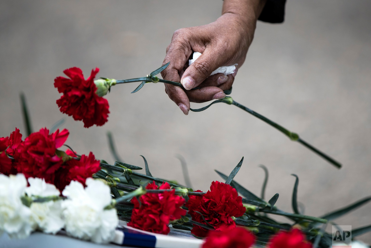 A woman places a flower on placards barring the names of loved ones during an annual ceremony for fallen police and fire personnel at the Living Flame Memorial in Philadelphia, Wednesday, May 3, 2017. (AP Photo/Matt Rourke)