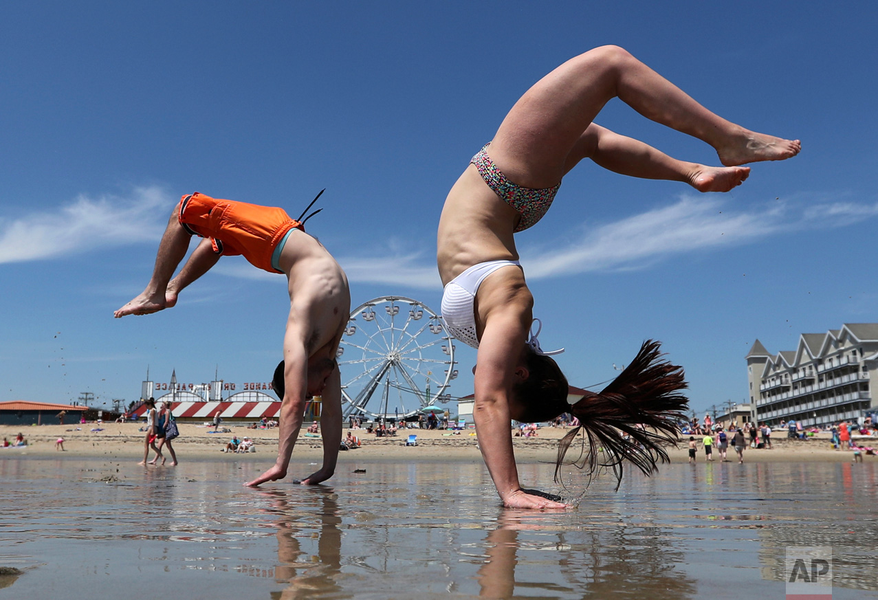 Dan Copeland, left, and Alex Morneau of Biddeford, Maine, former high school cheerleaders, perform back flips while enjoying the record breaking heat, Thursday, May 18, 2017, at Old Orchard Beach, Maine. The temperature climbed well into the 90s in many locations throughout the state. (AP Photo/Robert F. Bukaty)