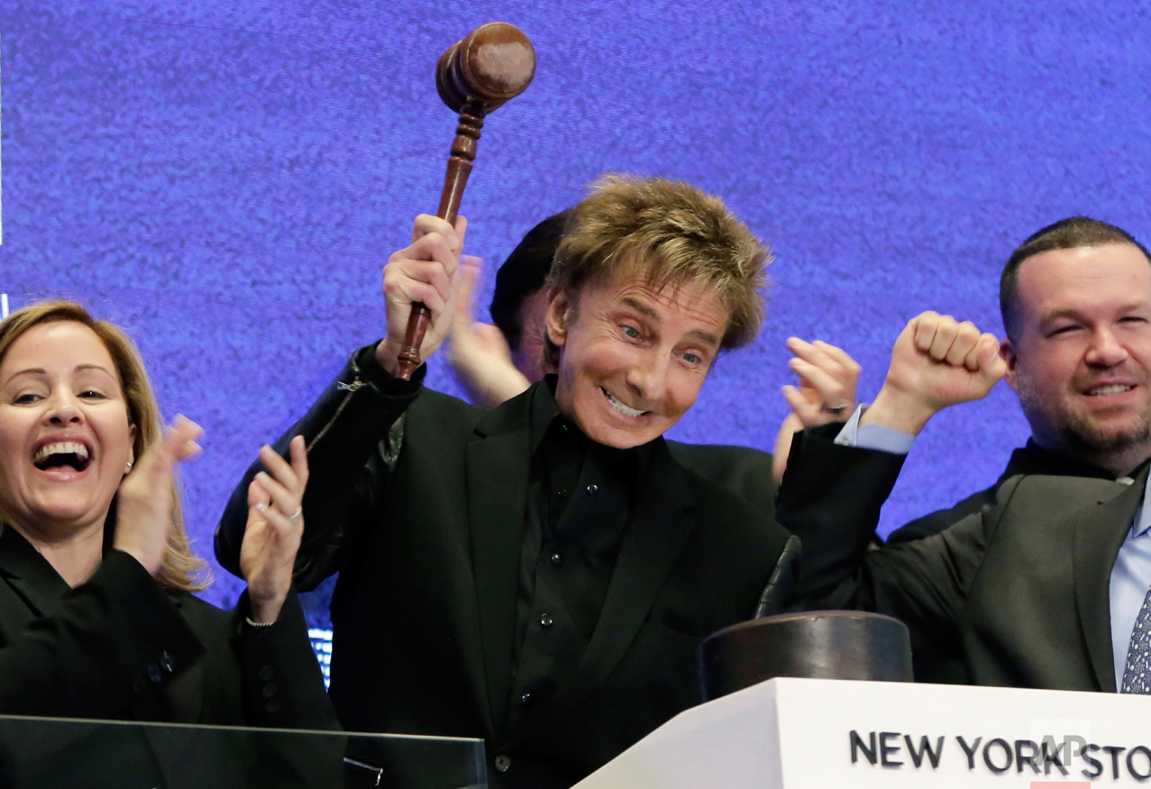 Singer Barry Manilow, center, gavels trading closed on the bell podium of the New York Stock Exchange, Friday, May 26, 2017. (AP Photo/Richard Drew)