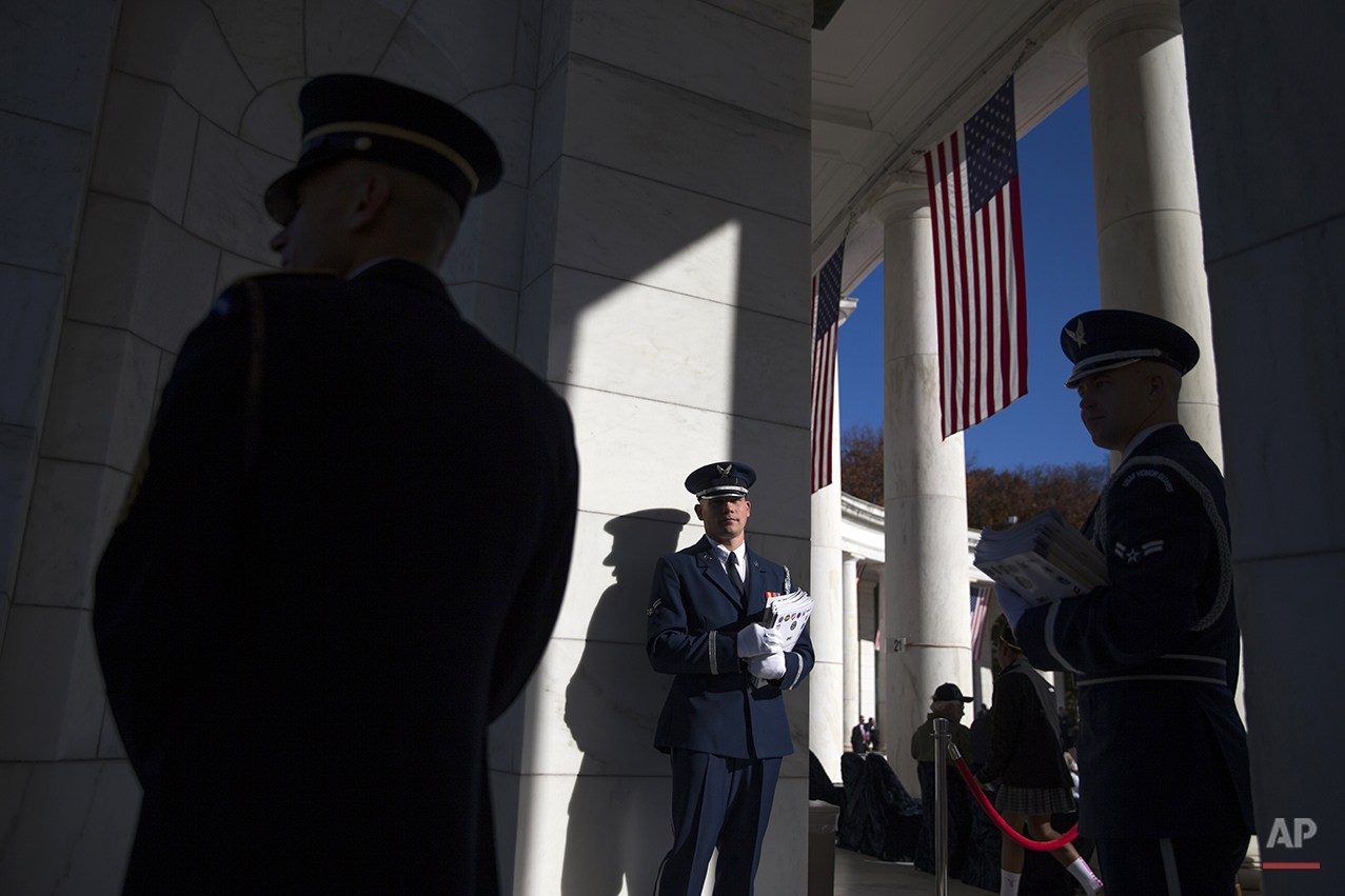 Airman Trevor O'Bryan waits for the arrival of visitors to the annual Veterans Day Observance Ceremony at Arlington National Cemetery, in Arlington, Va., Tuesday, Nov. 11, 2014. Americans marked Veterans Day on Tuesday with parades, speeches and military discounts, while in Europe the holiday known as Armistice Day held special meaning in the centennial year of the start of World War I.   (AP Photo/Evan Vucci)