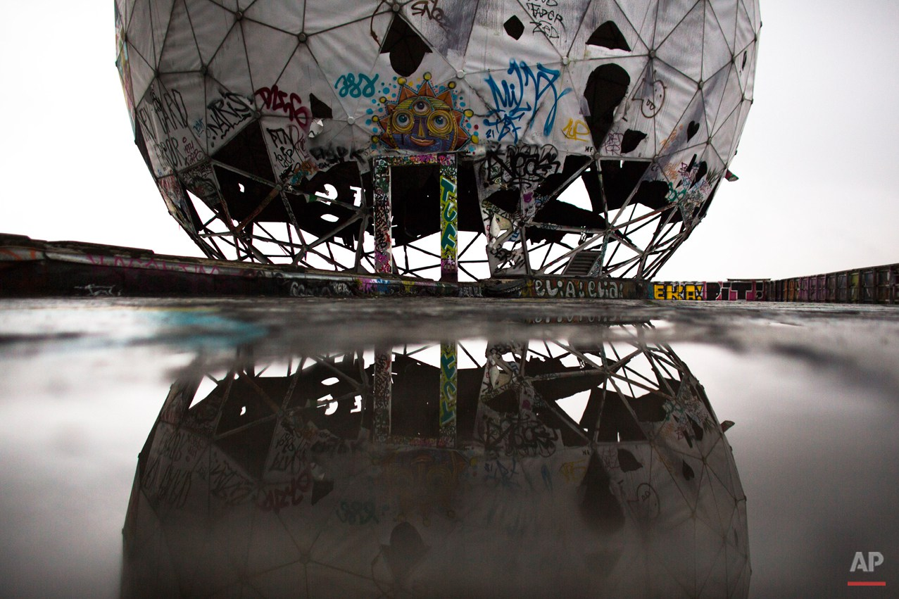 In this Oct. 16, 2014 photo, the ruin of a vandalized, golf ball-shaped cover for antennas of the abandoned former listening station of the United States National Security Agency, at the Teufelsberg (Devil's Mountain) is reflected in a puddle in Berlin. The listening station, which was active until the early '90s, is now used by graffiti artists and can be visited only with guided tours. (AP Photo/Markus Schreiber)