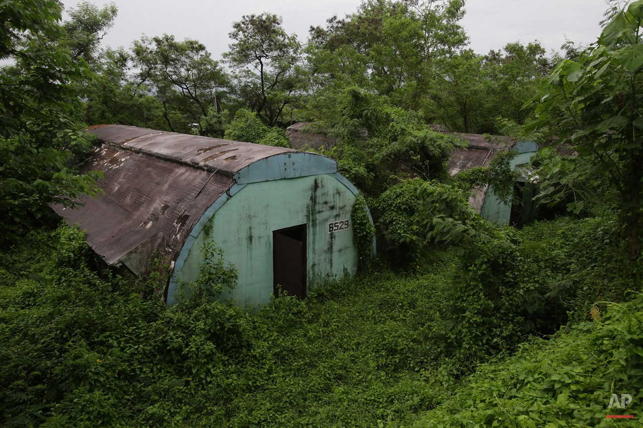 "In this Oct. 18, 2014, photo, a row of concrete structures called ""Quonset huts"" lie inside the Subic Bay Freeport Zone, Zambales province, northern Philippines. The huts were used as barracks for U.S. Marines inside the former American naval base. It was closed in 1992 after the Philippine Senate voted not to extend the lease on the facility. Some of the abandoned huts were reused as dormitories and staff houses for employees. Other abandoned huts have not been touched since U.S. forces left 22 years ago. (AP Photo/Aaron Favila)"