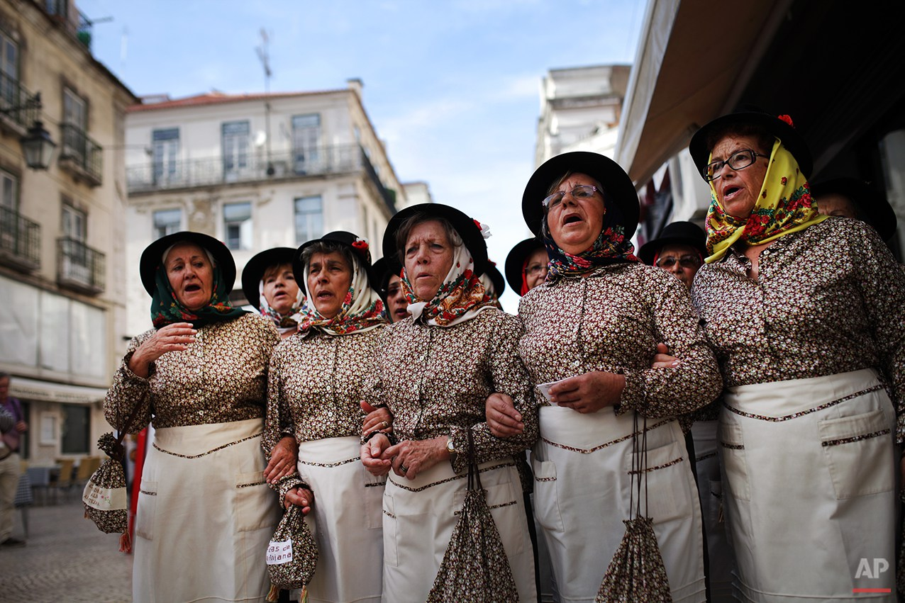 Women wearing traditional clothes from Portugal's Alentejo region sing an emigration folk song in downtown Lisbon, Portugal, Saturday, Oct. 25, 2014. (AP Photo/Francisco Seco)