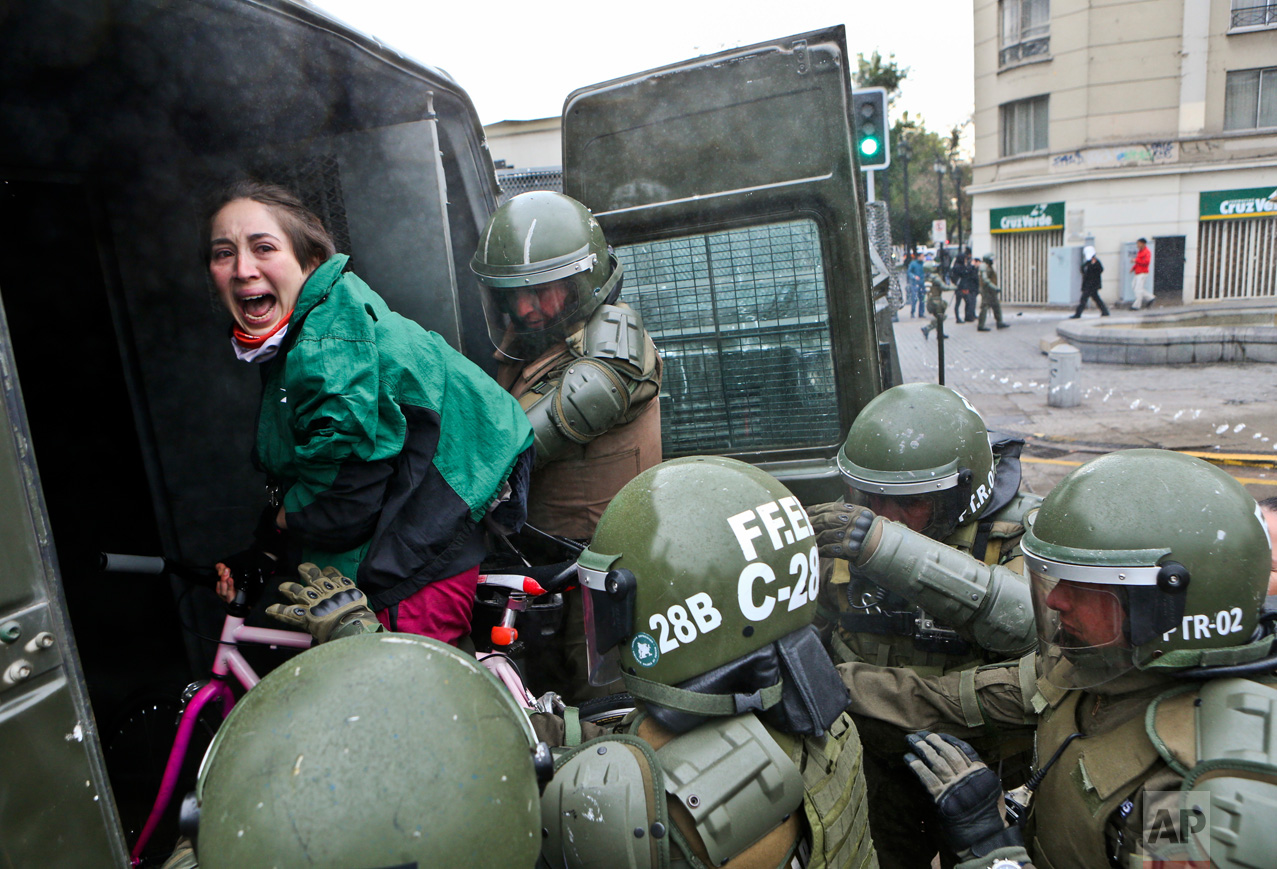 A woman on her bicycle is lifted and placed by police into a wagon during a protest march demanding the government overhaul the education funding system that would include canceling their student loan debt, in Santiago, Chile, Wednesday, June 21, 2017. (AP Photo/Esteban Felix)