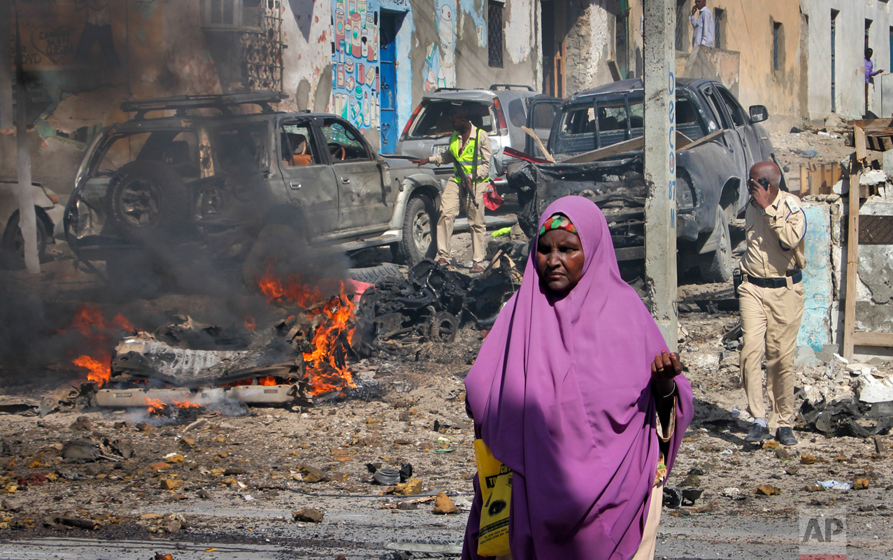 A woman walks past the scene of a suicide car bomb attack on a police station in Mogadishu, Somalia Thursday, June 22, 2017. A number of people are dead and several others wounded in the blast in Somalia's capital, police said Thursday, adding that the bomber was trying to drive into the police station's gate but detonated against a wall. (AP Photo/Farah Abdi Warsameh)
