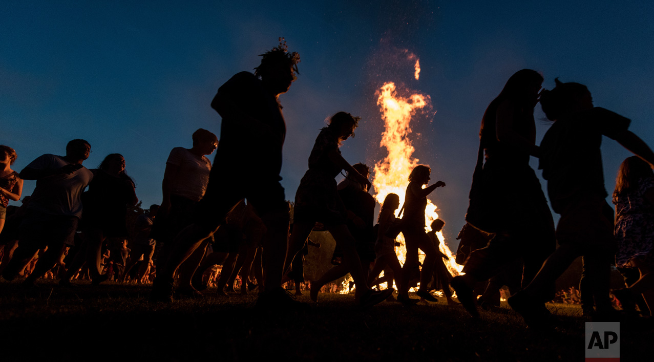 People dance around a bonfire during a solstice celebration in Freiburg, southern Germany on Wednesday, June 21, 2017. (Patrick Seeger/dpa via AP)