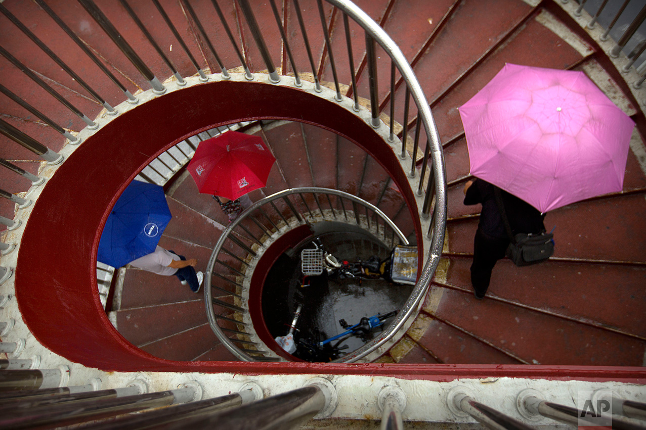 People holding umbrellas climb an outdoor staircase on a rainy day in Beijing, Thursday, June 22, 2017. Although Beijing is in a semi-dry climate, it receives much of its annual precipitation during the summer months. (AP Photo/Mark Schiefelbein)
