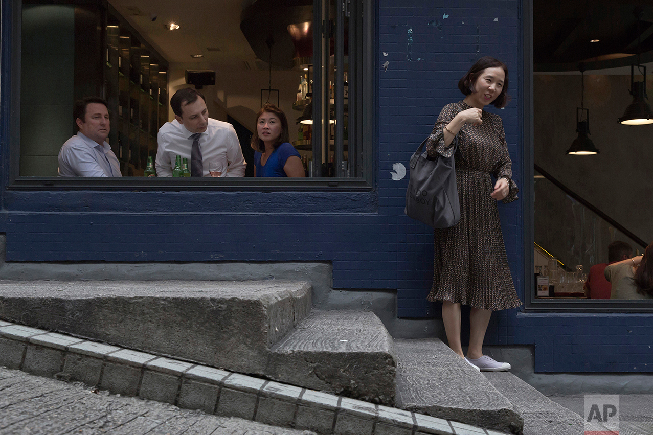 In this May 25, 2017, photo, a man inside a bar looks towards a woman in Central district, Hong Kong. (AP Photo/Kin Cheung)