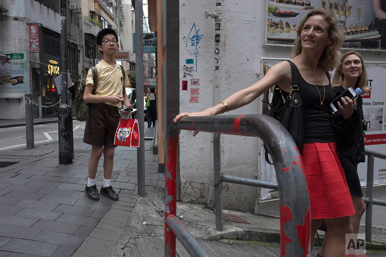 In this May 25, 2017, photo, a student stands as women walk down the slope in Central district, Hong Kong. (AP Photo/Kin Cheung)