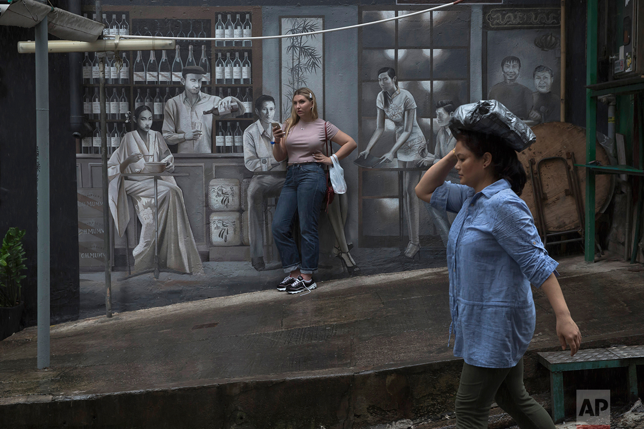 In this June 12, 2017 photo, a woman stands in front of a mural on the slope in Central district, Hong Kong. (AP Photo/Kin Cheung)