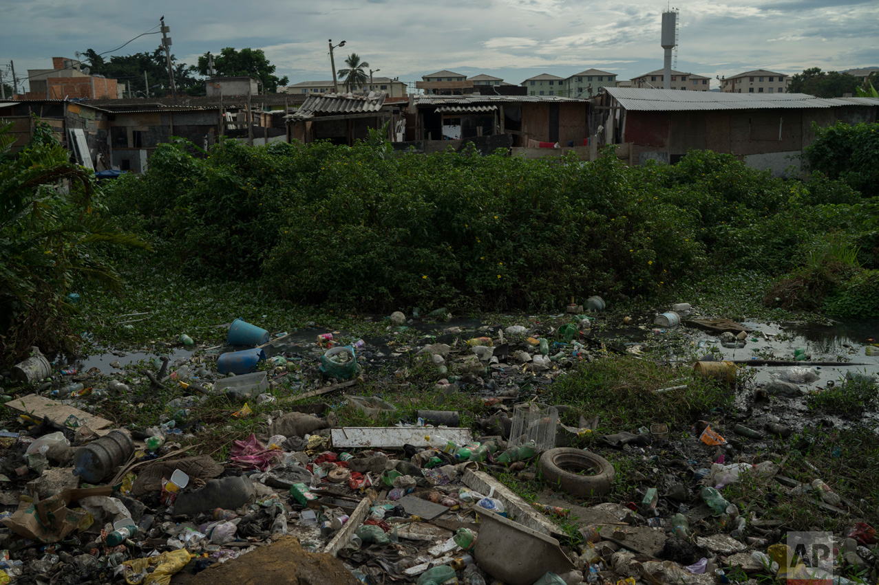 In this June 6, 2017 photo, open sewage is covered by trash near homes in the City of God slum of Rio de Janeiro, Brazil. (AP Photo/Leo Correa)