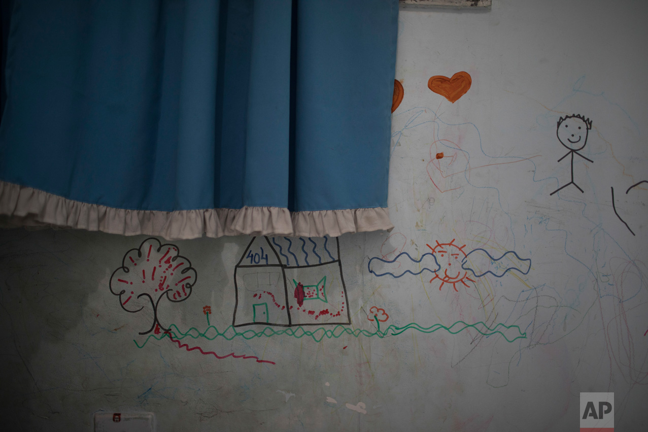 In this June 10, 2017 photo, drawings cover the wall of Isaac's room in the City of God slum of Rio de Janeiro, Brazil. (AP Photo/Leo Correa)