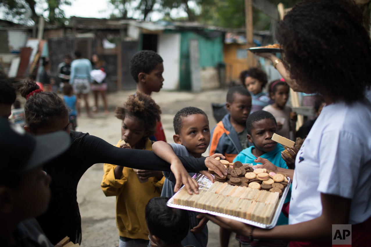 In this June 10, 2017 photo, kids help themselves to snacks being handed out by an NGO in one of the poorest area of the City of God slum in Rio de Janeiro, Brazil. (AP Photo/Leo Correa)