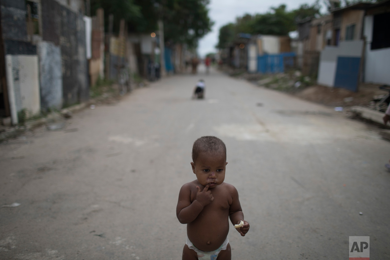 "In this June 10, 2017 photo, a baby with a piece of bread stands outside his home under the watch of his mother in the neighborhood ""Cantinho do Ceu"" which means in Portuguese ""Heaven's corner,"" one of the poorest areas of the City of God slum of Rio de Janeiro, Brazil. (AP Photo/Leo Correa)"