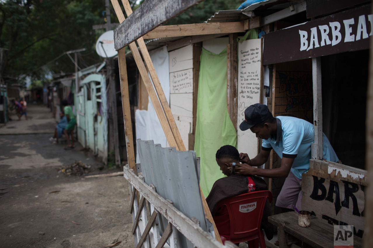 "In this June 10, 2017 photo, a barber cuts a client's hair at his shop in the ""Cantinho do Ceu"" neighborhood that means in Portuguese ""Heaven's corner,"" one of the poorest areas of the City of God slum in Rio de Janeiro, Brazil. (AP Photo/Leo Correa)"