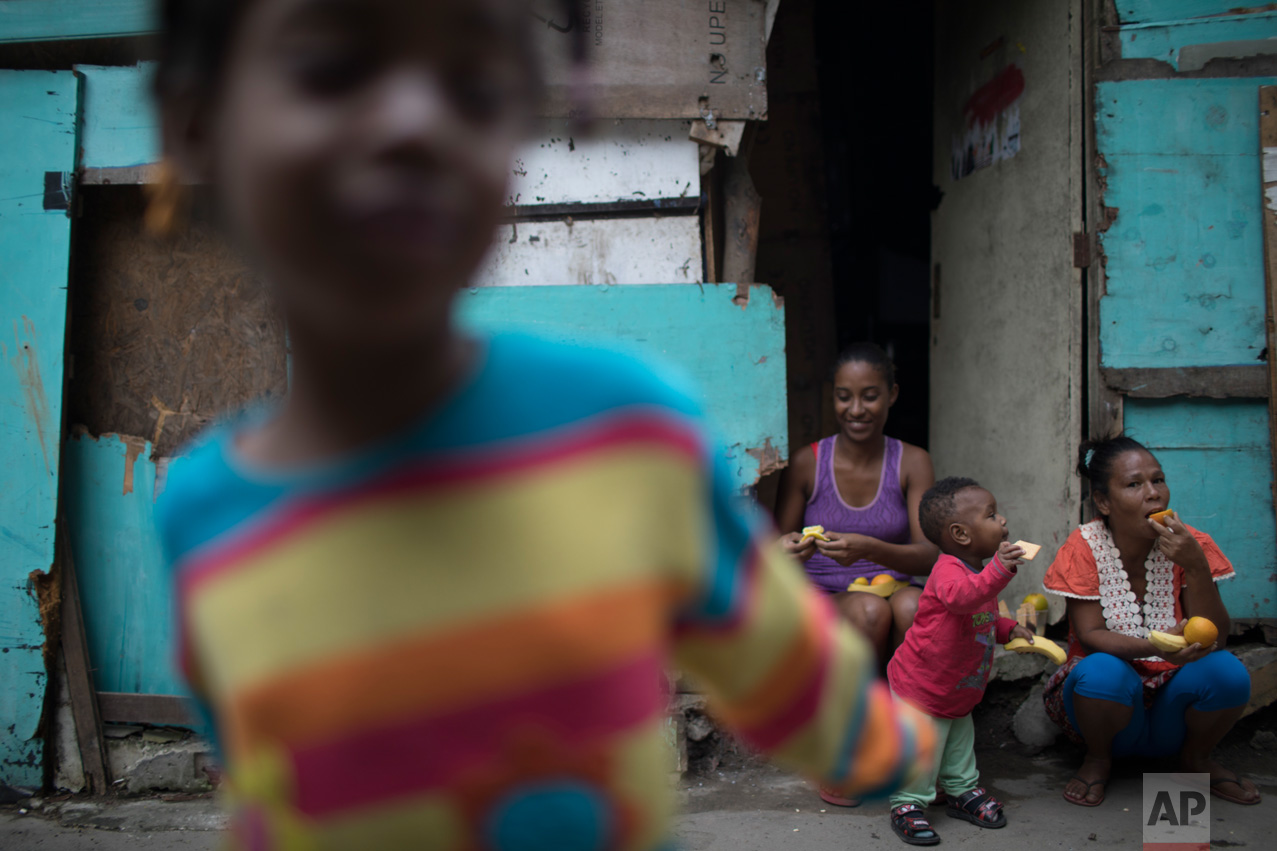 In this June 10, 2017 photo, women and children eat fruit distributed by an NGO in one of the poorest areas of the City of God slum in Rio de Janeiro, Brazil. (AP Photo/Leo Correa)