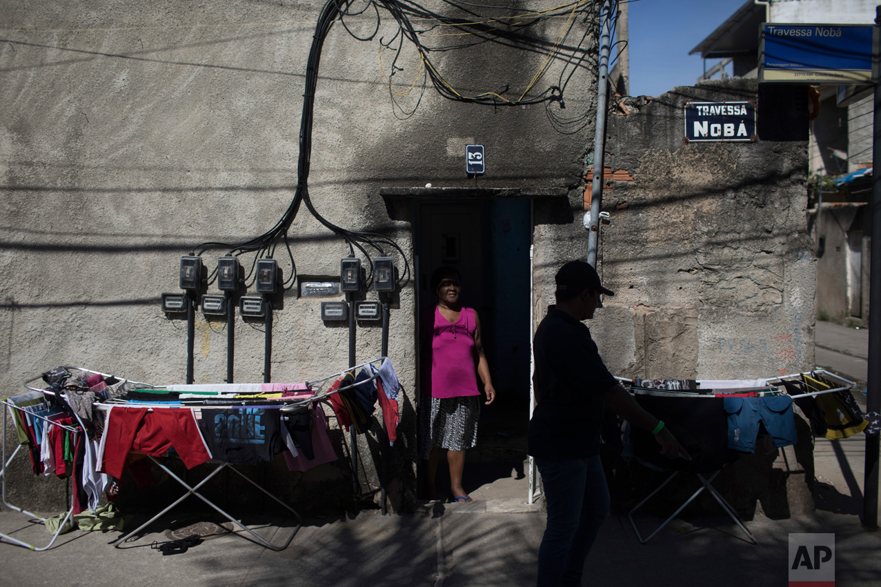 In this June 8, 2017 photo, evangelical pastor Silvio Cesar Soares Gonzaga is silhouetted as he walks past the home of Celina, an elderly woman who helped him after he left a life of drug trafficking in the City of God slum of Rio de Janeiro, Brazil. (AP Photo/Leo Correa)