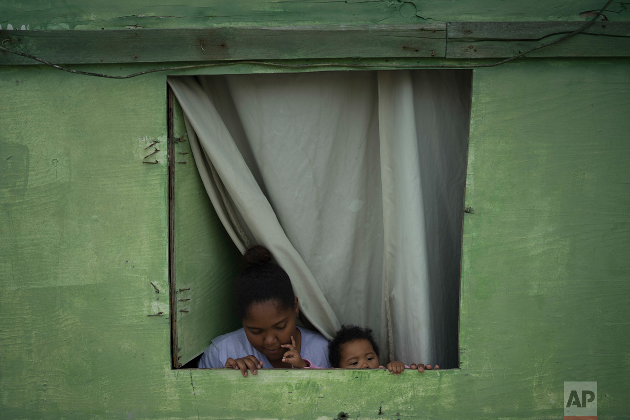 In this June 6, 2017 photo, Suzi Souza dos Santos and her baby Maria Lais stand in the window of their small wooden home in one of the poorest areas of the City of God slum in Rio de Janeiro, Brazil. (AP Photo/Leo Correa)