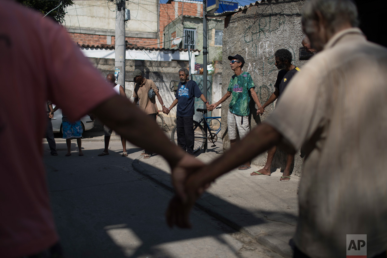 In this June 12, 2017 photo, men pray before eating a free meal provided by resident Ana Regina de Jesus in the City of God slum of Rio de Janeiro, Brazil. (AP Photo/Leo Correa)