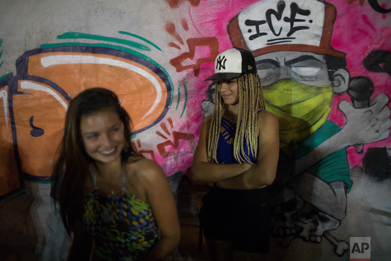 In this June 8, 2017 photo, young women attend a night session of rap battles in the City of God slum of Rio de Janeiro, Brazil. (AP Photo/Leo Correa)