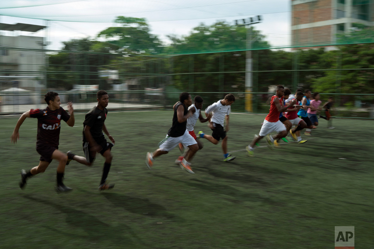 In this June 5, 2017 photo, youth warm up for soccer practice in the City of God slum of Rio de Janeiro, Brazil. (AP Photo/Leo Correa)
