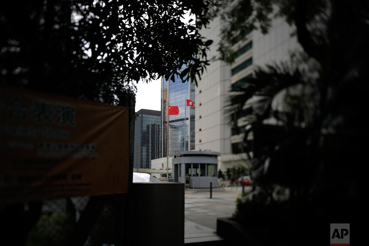 """In this June 12, 2017, photo made with a tilt-shift lens, a Chinese national flag and a Hong Kong flag are flown at the High Court in Hong Kong. Under the """"one country, two systems"""" principle, Hong Kong retains an independent judiciary, setting it apart from mainland China. Two decades since Beijing took control of Hong Kong, China's rising influence – and Britain's waning profile – are impossible to ignore. (AP Photo/Vincent Yu)"""