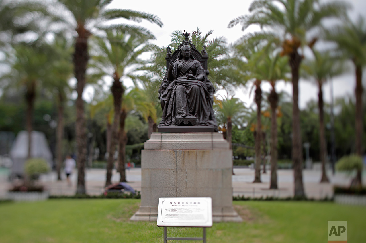 In this June 4, 2017, photo made with a tilt-shift lens, a statue of Britain's Queen Victoria is seen at Victoria Park in Hong Kong. The park near the Causeway Bay downtown shopping district has been the rallying point for the annual pro-democracy march and vigil to remember victims of the bloody 1989 military crackdown on protesters in Beijing's Tiananmen Square. Two decades since Beijing took control of Hong Kong, China's rising influence – and Britain's waning profile – are impossible to ignore. (AP Photo/Vincent Yu)