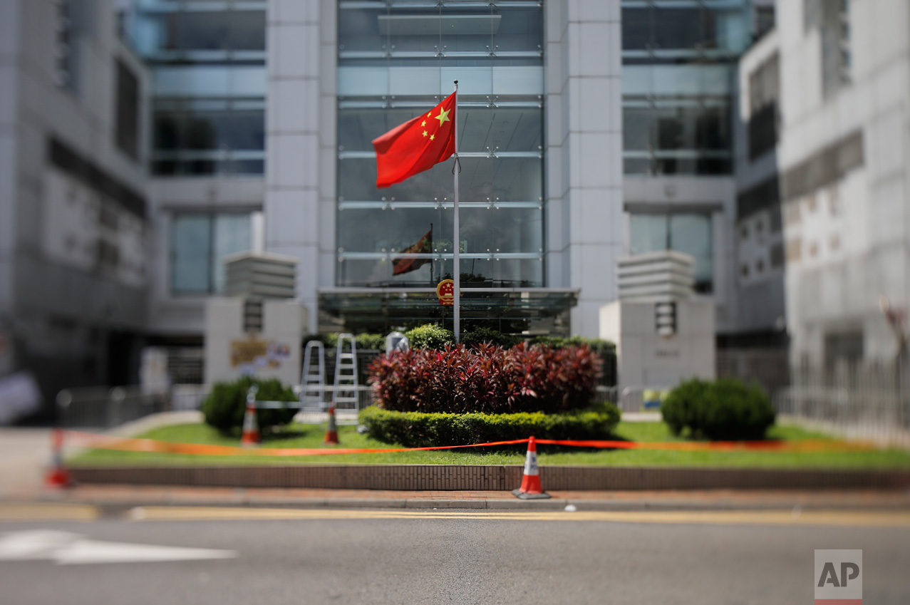 In this June 27, 2017, photo made with a tilt-shift lens, a Chinese national flag is flown at the the Chinese central government's Liaison Office in Hong Kong. The office is a frequent target of protests by pro-democracy supporters, who believe that officials stationed there are the real power in Hong Kong. Two decades since Beijing took control of Hong Kong, China's rising influence – and Britain's waning profile – are impossible to ignore. (AP Photo/Vincent Yu)