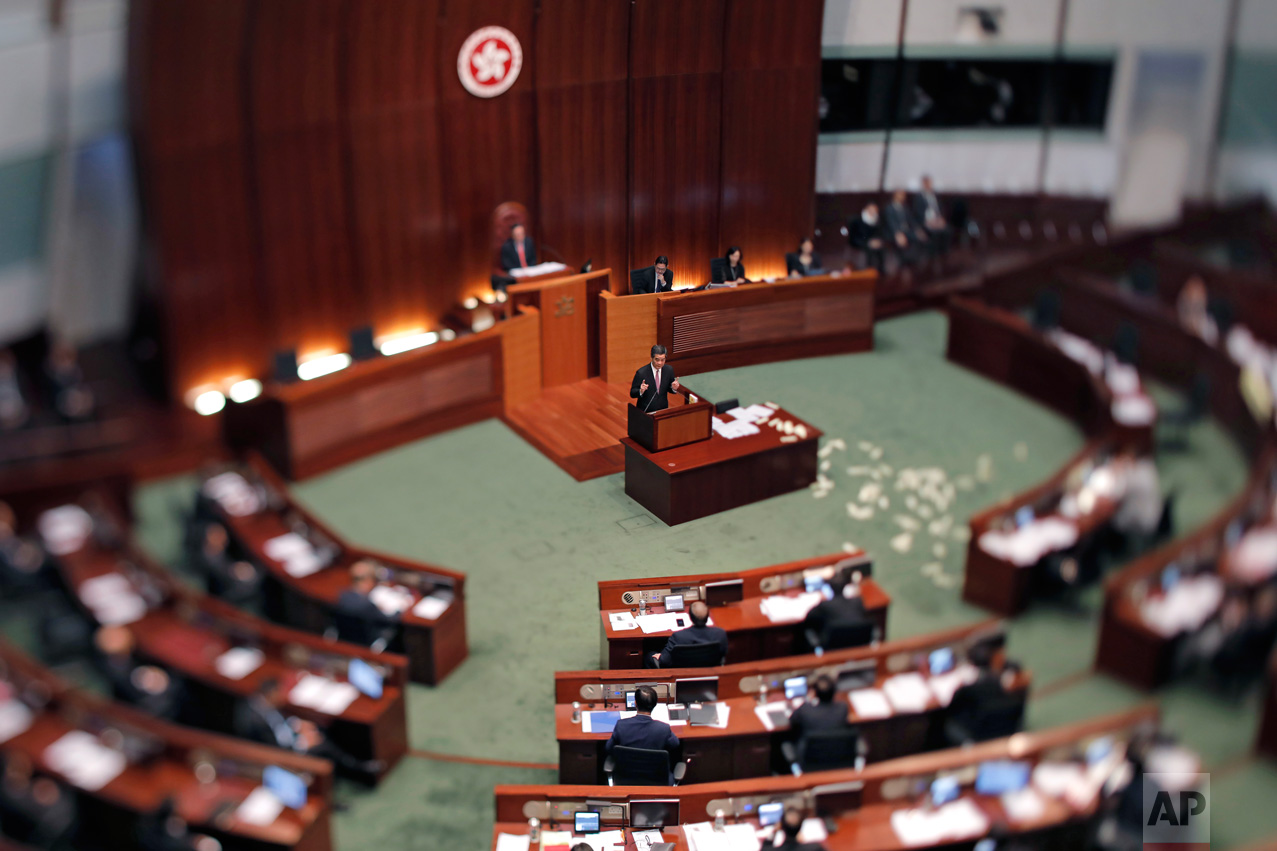 """In this June 1, 2017, photo made with a tilt-shift lens, Hong Kong Chief Executive Leung Chun-ying, center, speaks after lawmaker Leung Kwok-hung, also known as Long Hair threw """"hell money"""" during his last question-and-answer session at the legislative council in Hong Kong. Hong Kong's departing leader, Leung Chun-ying, also known as CY, is viewed by pro-democracy activists as a puppet of Beijing. Two decades since Beijing took control of Hong Kong, China's rising influence – and Britain's waning profile – are impossible to ignore. (AP Photo/Vincent Yu)"""