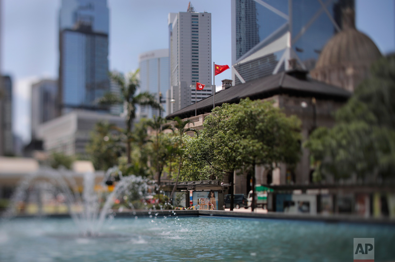 """In this May 31, 2017, photo made with a tilt-shift lens, a Chinese national flag and a Hong Kong flag fly at the Court of Final Appeal in Hong Kong. Under the """"one country, two systems"""" principle, Hong Kong retains an independent judiciary, setting it apart from mainland China.(AP Photo/Vincent Yu)"""