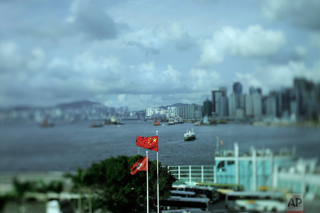 In this June 8, 2017, photo made with a tilt-shift lens, a Chinese national flag and a Hong Kong flag are flown as Victoria Harbor is seen at rear in Hong Kong. Hong Kong's famous waterfront retains its British colonial-era name and was the scene of Britain's farewell from its colony in 1997. Two decades since Beijing took control of Hong Kong, China's rising influence – and Britain's waning profile – are impossible to ignore. (AP Photo/Vincent Yu)